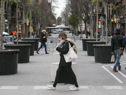 Una joven pasea por el cruce de las calles Marina y Mallorca, junto a la Sagrada Familia.