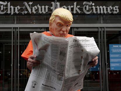 El activista Mike Hisey, disfrazado como Trump vestido con un traje de prisión leyendo el 'Times' frente a la puerta del diario neoyorquino, este lunes.