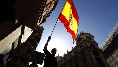 Un manifestante con una bandera española en una protesta en Barcelona