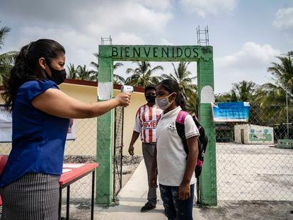Aracely Muñoz toma la temperatura de Rubisela Hernández, alumna de la escuela Venustiano Carranza, ubicada en el municipio de Champotón, Campeche.
