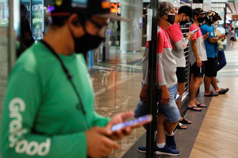 Repartidores de comida esperan pedidos en un centro comercial de Singapur.