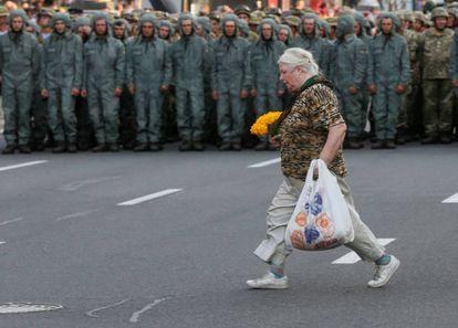 Una mujer cruza una calle frente a un cordón de militares, el lunes en el centro de Kiev.
