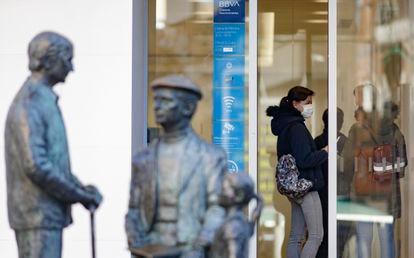 Una mujer saca dinero, durante el primer día laborable desde que se decretó el estado de alarma, este lunes en Madrid.