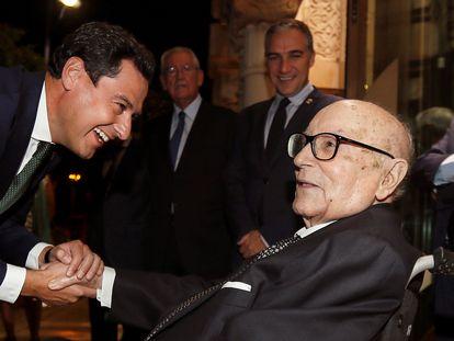 El presidente del Gobierno de Andalucía, Juanma Moreno, saluda al profesor Manuel Clavero Arévalo, antes del homenaje que Clavero recibió en julio de 2019.