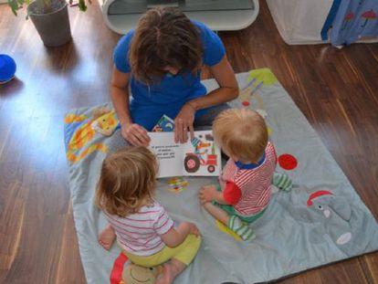 Diana Perazzini, madre de día, lee un cuento a Nina y a Lucas antes de la siesta. EDP