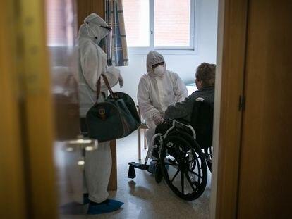 Una voluntaria de la ONG Proactiva Open Arms y una trabajadora de una residencia, durante el traslado de una mujer mayor en Barcelona el pasado 18 de abril.