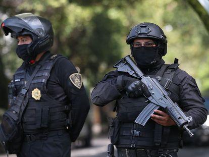 Dos agentes de la policía capitalina resguardan la zona del atentado por parte de un grupo armado al secretario de seguridad ciudadana, Omar García Harfuch, la mañana del 27 de julio de 2020 en Ciudad de México (México).