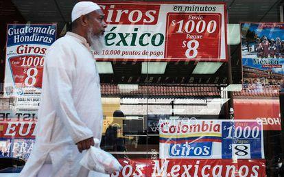 Un hombre camina delante de una tienda especializada en viajes y envío de dinero a Latinoamérica.