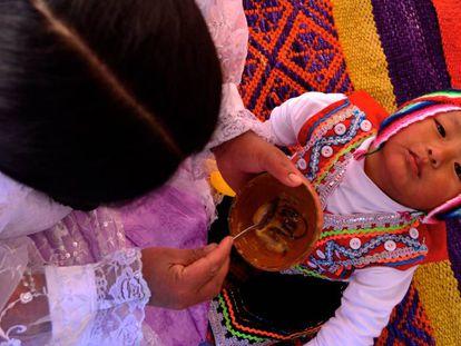 Lidia Dueñas le da de comer a su hijo en el rincón de juegos que tiene en su casa en Lucre (Quispicanchi, Cuzco, Perú).