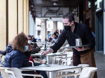 Un camarero sirve un café a una clienta en Badajoz, Extremadura (España).