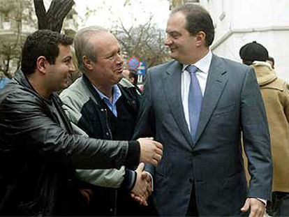 Costas Karamanlís recibe la felicitación de dos ciudadanos por su victoria electoral, ayer en Atenas.