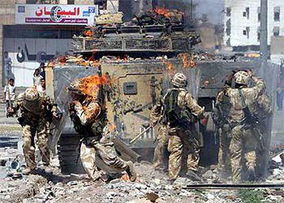 Un soldado británico corre cubierto por las llamas tras las violentas protestas ocurridas ayer en Basora.