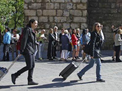 Dos mujeres pasan con sus maletas junto al Alcázar de Sevilla.