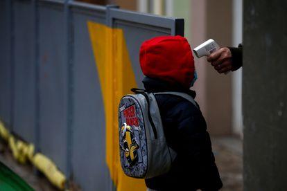 Una profesora toma la temperatura a un alumno de una escuela de Barcelona antes de entrar a clase.