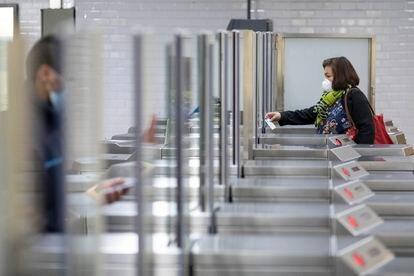Algunos ciudadanos vuelven al trabajo en transporte público y pasan por la estación de metro Passeig de Gracia en Barcelona.