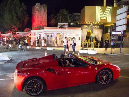 Un Ferrari circula frente a la discoteca Mirage, cerrada, y el Sunset Café, en Puerto Banús (Marbella).