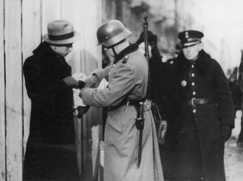 Soldados alemanes y miembros de la Policía Azul controlan la entrada del Gueto de Varsovia en 1941.