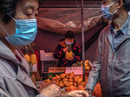 Personas protegidas con mascarillas en el interior de un mercado en Pekín (China).