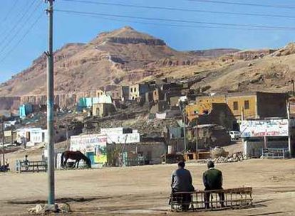 Imagen de Qurna. Delante, los edificios en curso de demolición. Detrás, la montaña piramidal llamada El Qurn, sagrada para los antiguos egipcios.