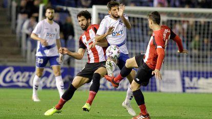 Dani García despeja el balón ante Alonso y Raúl García.