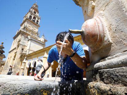 Un hombre se refresca en una fuente céntrica de Córdoba debido a las altas temperaturas.