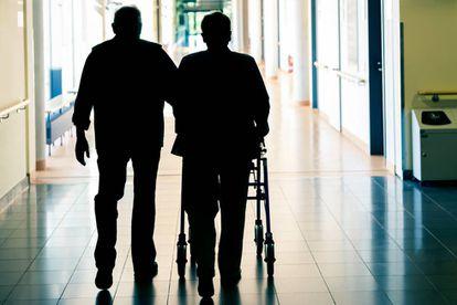 Una pareja de personas mayores camina con un andador.