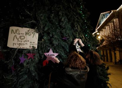 Dos mujeres colocan en un árbol de Navidad de la Plaza del Castillo en Pamplona dos estrellas, una de ellas con el nombre de Laura Luelmo y la otra con el numero de mujeres asesinadas este año.