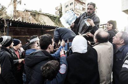 Varios habitantes de Damasco se apiñan ante un vendedor de agua embotellada.