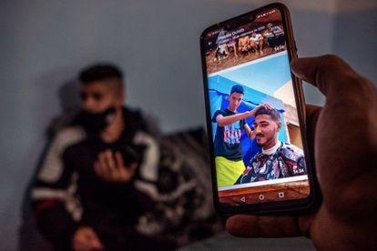 Mohamed Bouhafra muestra una foto en la que su amigo Hossine Ochlih le corta el pelo.