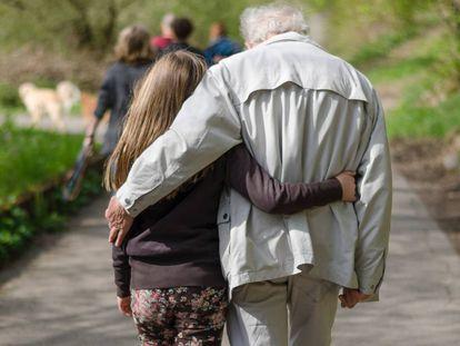 Una nieta camina agarrada de su abuelo.