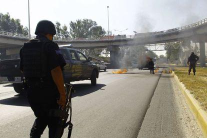 Bomberos y policía estatal apagan uno de los vehículos incendiados.