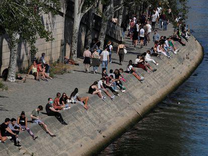 Personas sentadas a la orilla del Sena, en París, el domingo.