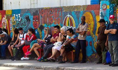 Un grupo de personas esperando en una parada de ómnibus.