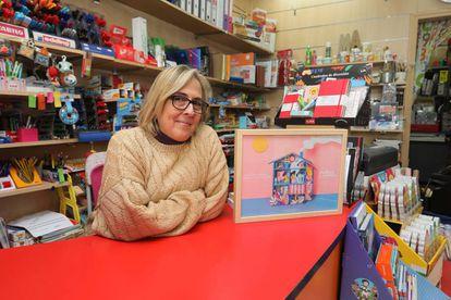 Cristina Herrero en su negocio, la papelería Mashe, con el cartel.