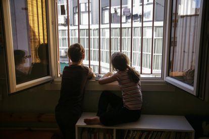 Los niños, durante el confinamiento. Dos hermanos miran por la ventana de su dormitorio, en Madrid, durante las semanas en las que no se podía salir salvo por desplazamiento justificado.