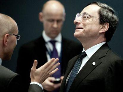 El presidente del BCE, Mario Draghi, conversa con un miembro del comité ejecutivo del banco.