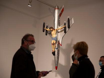 Varios visitantes, ante 'La civilización occidental y cristiana', obra de León Ferrari, en la muestra dedicada al artista en el Reina Sofía.