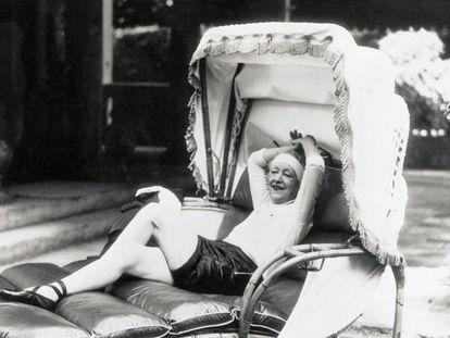 """Elsie de Wolfe se relaja tras una sesión de gimnasia en su residencia parisina Villa Trianon, para un reportaje tras su matrimonio Sir Charles Mendl titulado """"La vida comienza a los 65"""".  """