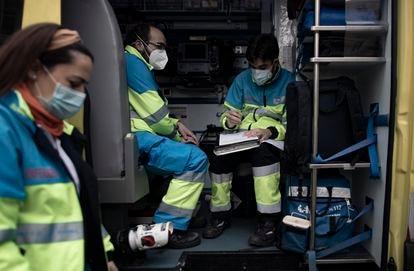 Varios trabajadores sanitarios de una UVI móvil del SUMMA 112 hacen anotaciones durante su jornada de trabajo el pasado viernes en Madrid.