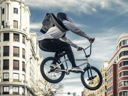 Un hombre tranquilo vuela sobre una bicicleta por las calles de Madrid.