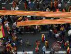 People hold a Catalan flag, known as Senyera, as they march during a demonstration in favour of a unified Spain a day before the banned October 1 independence referendum, in Barcelona