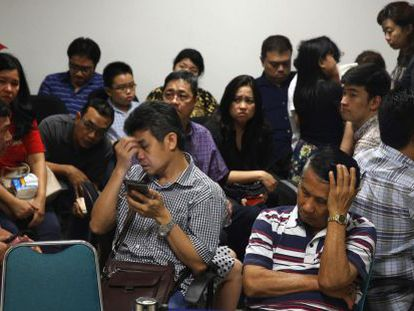 Familiares de los pasajeros del avión desaparecido esperan noticias en el aeropuerto de Surabaya.