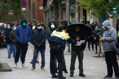 Una agente informa a personas hacen cola en el Centro de Servicios Sociales del barrio del Raval de Barcelona.