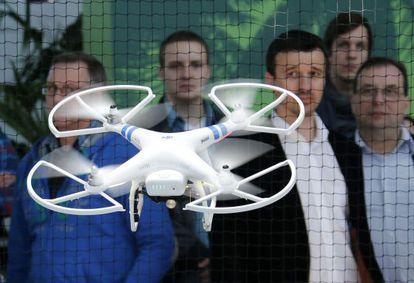 Los asistentes a la feria CeBIT de Hanover (Alemania) contemplan un dron Phantom 2.