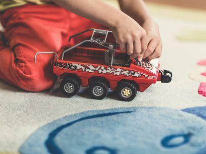 Un niño juega con su lancha de juguete en casa.