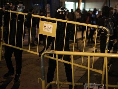 Unos jóvenes cargan unas vallas en la quinta noche de protestas por el encarcelamiento del rapero Pablo Hasél, el sábado.