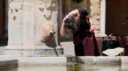 Una mujer se refresca en Córdoba.