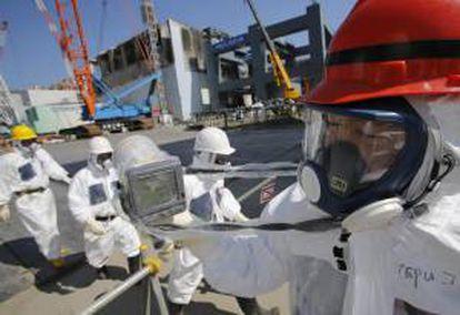 Un trabajador de la operadora Tokyo Electric Power (TEPCO) sostiene un monitor de radiación junto al reactor número 4 (atrás izq) durante una visita a la planta nuclear de TEPCO en Fukushima, Japón. EFE/Archivo