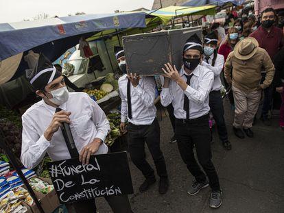 El candidato a la asamblea constituyente Daniel Andrade, a la izquierda, participa en una actuación callejera llamada 'Funeral de la Constitución' en referencia a la constitución de la era militar de Chile, mientras hace campaña en un mercado al aire libre en Santiago, Chile, el pasado sábado 8 de mayo de 2021.