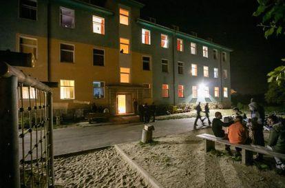 Varios demandantes de asilo esperan frente al refugio de Saalfeld (Alemania) tras el incendio en el que murió una persona.